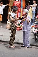 Hanoi<br /> , Vietnam - 2007 File Photo -<br /> <br /> A Vietnamese grandmother giving treats to grandchild, while mother carries. <br />  in Hanoi street.<br /> <br /> <br /> photo : James Wong-  Images Distribution