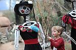 Foto: VidiPhoto<br /> <br /> ARNHEM - Kinderen mogen maandag met een plumeau een handje helpen bij het afstoffen van de ietwat griezelige skeletten in de Desert van Burgers' Zoo. De Mexicaanse variant op Halloween (Dia de los Muertos) is een enorme succes in de herfstvakantie, maar de woestijn is wel enorm stoffig. De feestelijk versierde en lachende schedels en poppen moeten daarom regelmatig schoongemaakt worden. Maandag mochten kinderen dat doen. Het succes is zo groot dat vandalen met enige regelmaat maskers of andere onderdelen van de poppen roven en mee naar huis nemen. Wellicht om zelf te gebruiken voor Halloween. Waar Halloween vooral als doel heeft om angst aan te jagen, is Dia de los Muertos (Dag van de doden) kleurrijker, vrolijker, muzikaler en historischer. Het feest van de doden, dat tot 30 oktober duurt, is ge&iuml;nspireerd op de culturen van de Azteken en Maya's, die hun overleden voorouders en familieleden met speciale ceremonies eerden en tevens het leven vierden. De Mexicanen geloven dat op 1 en 2 november (Allerheiligen en Allerzielen) de zielen van overleden vrienden en familieleden weer voor even terug komen. Ze vieren dit met een groot feest.