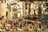 Sun bathers on beach at Cefalu, Sicily, Italy