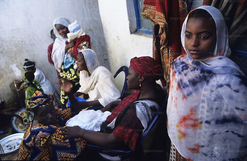 Husa Muslim women in conversation at home in their courtyard..The implementation of Islamic Sharia Law across the twelve northern states of Nigeria, centres upon Kano, the largest Muslim Husa city, under the feudal, political and economic rule of the Emir of Kano. Islamic Sharia Law is enforced by official state apparatus including military and police, Islamic schools and education, plus various volunteer Militia groups supported financially and politically by the Emir and other business and political bodies. Fanatical Islamic Sharia religious traditions  are enforced by the Hispah Sharia police. Deliquancy is controlled by the Vigilantes volunteer Militia. Activities such as Animist Pagan Voodoo ceremonies, playing music, drinking and gambling, normally outlawed under Sharia law exist as many parts of the rural and urban areas are controlled by local Mafia, ghetto gangs and rural hunters. The fight for control is never ending between the Emir, government forces, the Mafia and independent militias and gangs. This is fueled by rising petrol costs, and that 70% of the population live below the poverty line. Kano, Kano State, Northern Nigeria, Africa
