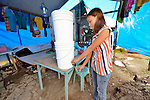 Maria Zayra Solis gets clean water from a water filter in her family's temporary home in Tanauan, a city in the Philippines province of Leyte that was hit hard by Typhoon Haiyan in November 2013. The storm was known locally as Yolanda. Hundreds of families here received water filters from the United Methodist Committee on Relief, a member of the ACT Alliance. UMCOR is also working with city officials to help residents here build permanent houses to replace those they lost in the storm.