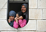 Souad Kasem Issa and her daughters Rawan, 10, and Rahaf, 9, look out a window of the apartment where they live in Amman, Jordan. The family of eight fled the city of Homs, Syria, as fighting there worsened in 2012. Their home in Syria has since been destroyed by bombing, and they are struggling to survive in Jordan's capital city. They are receiving some assistance from International Orthodox Christian Charities, is a member of the ACT Alliance.