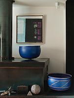 Pots by Alev Ebuzziya Siesbye flank the iron/epoxy fireplace in the living room, bringing a dash of colour to the black scrubbed surfaces