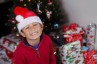 Boy with Santa Hat in front of Christmas tree with lights and decorations - with copy space to right