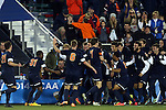 12 December 2014: Virginia players mob Darius Madison on in front of the bench after his first half goal. The University of Virginia Cavaliers played the University of Maryland Baltimore County Retrievers at WakeMed Stadium in Cary, North Carolina in a 2014 NCAA Division I Men's College Cup semifinal match.