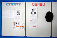 Items on the bulletin board at the Chernobyl Semikhody radiation checkpoint include two obituaries, details about a volleyball tournament, an ad for a taxi company and a lost hat.  <br /> ------------------- <br /> This photograph is part of Michael Forster Rothbart's After Chernobyl documentary photography project.<br /> &copy; Michael Forster Rothbart 2007-2010.<br /> www.afterchernobyl.com<br /> www.mfrphoto.com <br /> 607-267-4893 o 607-432-5984<br /> 5 Draper St, Oneonta, NY 13820<br /> 86 Three Mile Pond Rd, Vassalboro, ME 04989<br /> info@mfrphoto.com<br /> Photo by: Michael Forster Rothbart<br /> Date:  2/2009    File#:  Canon 5D digital camera frame 57452 <br /> ------------------- <br /> Original caption: .The Chernobyl Nuclear Power Plant (ChNPP or ChAES) is the site of the world's worst nuclear accident. On the night of April 26, 1986, the Fourth Block reactor exploded during a safety test, sending radioactive particles into the atmosphere and eventually around the world. The population within 30 kilometers was permanently evacuated, including residents of Pripyat and many villages. Although ChAES stopped generating electricity in December 2000, today 3,800 employees continue to work at the plant, commuting from the new city of Slavutich (population 24,300), which was built after the accident to replace Pripyat..