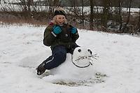 Kinder bauen einen Seehund, Robbe aus Schnee, Junge reitet auf seinem Schneetier
