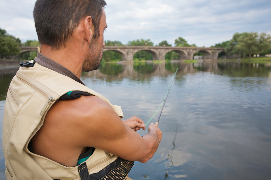 Flyfisherman Alain Luzuy waiting for a fish to take his dry fly in the river Allier. Pont-du-Chateau, France.
