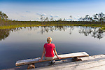 Young Woman Sitting by Lake, Viru Bog, Lääne-Viru County, Estonia, Europe