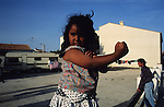 A young girl flexes her muscles in a camping site, during the Gypsy pilgrimage of Saintes Maries de la Mer. Camargue, France