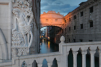 The Ponte dei Sospiri or Bridge of Sighs, 1600, designed by Antonio Contino, Venice, Italy. The bridge spans the Rio di Palazzo and connects the New Prison or Prigioni Nuove to the interrogation rooms in the Doge's Palace. The enclosed limestone bridge is so named as this would be the last view of Venice for prisoners on the way to their cells. On the left is a sculpture of the Drunkenness of Noah by Filippo Calendario from the corner of the Doge's Palace or Palazzo Ducale, begun 1340 and built in Venetian Gothic style. The city of Venice is an archipelago of 117 small islands separated by canals and linked by bridges, in the Venetian Lagoon. The historical centre of Venice is listed as a UNESCO World Heritage Site. Picture by Manuel Cohen