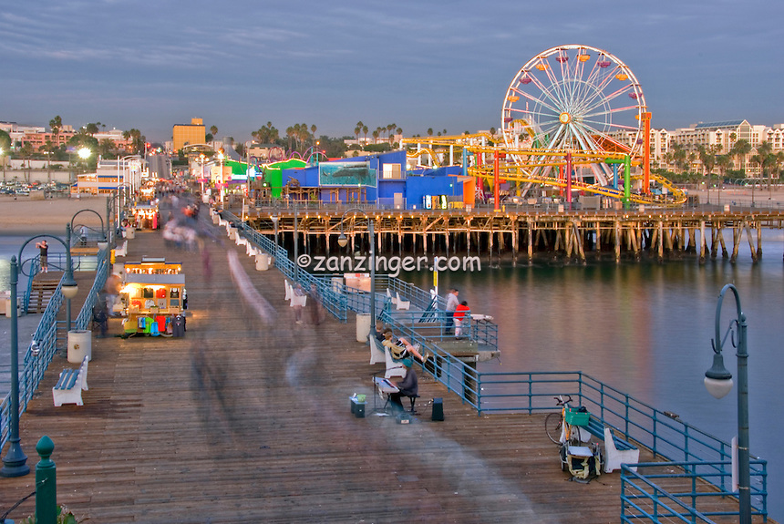Santa Monica CA Pacific Pier People moving near sunset, family amusement park large New Pacific Ferris wheel Roller Coaster moving over the ocean