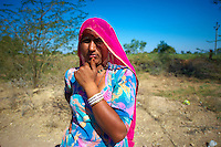 A Rajasthani woman standing by the road, waiting for a vehicle to take her to the next village.