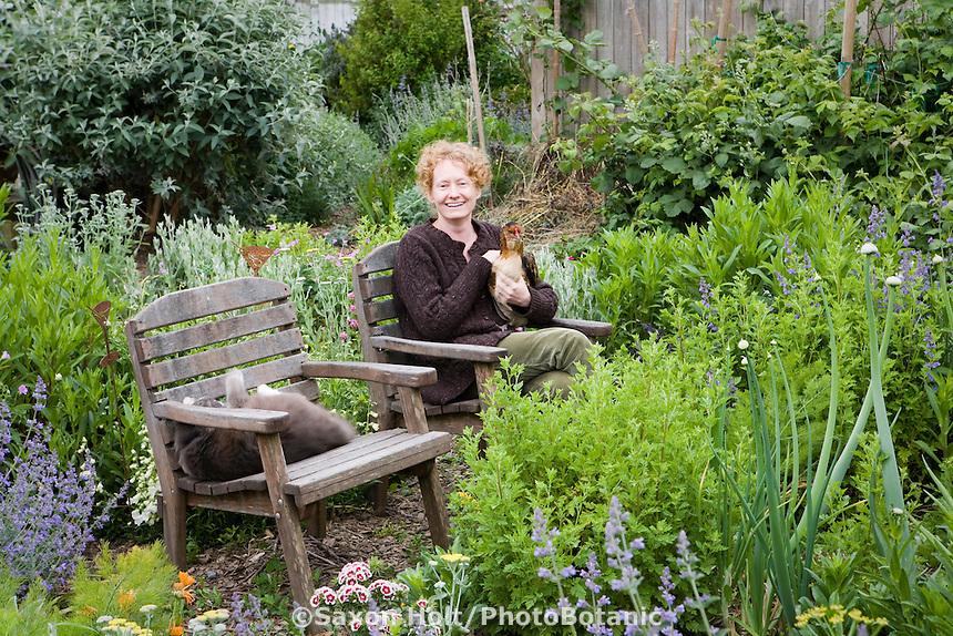 Amy Stewart sitting on chair holding chicken in her backyard garden