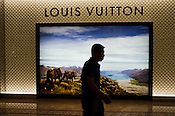 A Chinese man walks past a Louis Vuitton signage in a shopping centre in Central Macau, China.