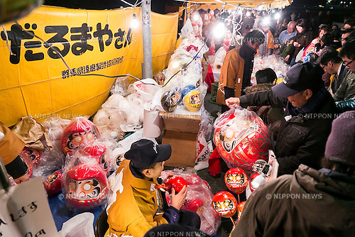 Merchants sale Daruma dolls outside the Shorinzan Daruma Temple in Takasaki City, Gunma Prefecture on January 6, 2016, Japan. Every year thousands of people visit the country's most famous Daruma market (Daruma ichi) held at the Shorinzan Daruma Temple on January 6 and 7. Takasaki City, is known as the capital of Daruma dolls and about 80% of Japan's Daruma are produced there. According to the tradition, Daruma dolls are sold without pupils painted on their eyes. People color in one pupil when a wish is made or a goal set, and when the wish comes true or the goal is achieved they fill in the other pupil. At the end of the year, used Daruma dolls are returned to the temple to be burned. (Photo by Rodrigo Reyes Marin/AFLO)