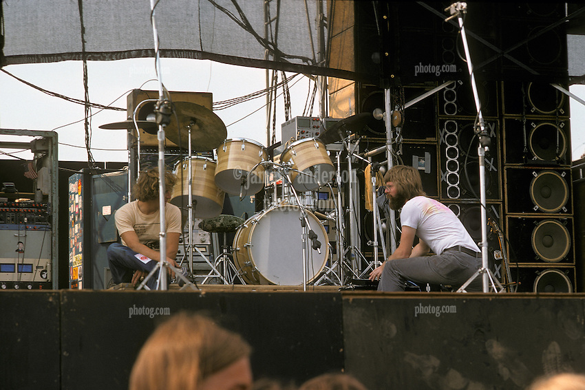 Phil Lesh and Ram Rod in conversation on stage before the Grateful Dead Play Live at Dillon Stadium, Hartford, CT 31 July 1974. Featuring the Wall of Sound. Summer weekday show, one of the longest ever played by The Dead. Deadheads hanging out, Crew setting up.