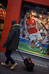 Diagonal angle of Arsenal footballer and man pulling luggage, in Carnaby Street, London.
