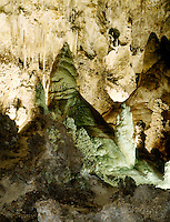 STALACTITES &amp; STALAGMITES IN LIMESTONE CAVERN<br /> Queen's Chamber, Soda Straws and Flowstone<br /> Calcium carbonate deposits (Stalactites) hang from the top of limestone caverns, formed by the dripping of mineralized solutions. Corresponding columnar deposits (Stalagmites) are built upward. Queens Chamber, Carlsbad.