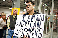 "Jose Antonio Vargas, a former journalist for the Washington Post who recently outed himself as an undocumented immigrant to the United States, holds a sign reading ""I am an american w/o papers"" at a campaign event with Republican presidential candidate Mitt Romney at the Diamond V South Plant on Friday, December 9, 2011 in Cedar Rapids, IA."