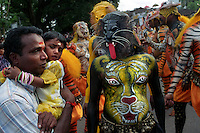 A Pulikali performer frightens a child during the performance at Swaraj road in Trichur, Kerala, India..Pulikali or Kaduvvakali is a two hundred year old folk dance form, practised mostly in Thrissur and Palghat districts of Kerala. It liberally makes use of forms and symbols of nature that finds expression in its bright, bold body painting and high-energy dance movements. The philosophy of Pulikali is that human and nature are integral parts of each other. So by fusing man and beast in its artistic language, it flamboyantly celebrates the connection. Arindam Mukherjee