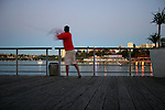 A man fishing early in the morning from the Manly Wharf.