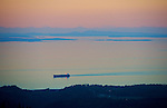 A ship heads towards Port Angeles in the Strait of San Juan de Fuca at sunset. The San Juan Islands and Canada are in the background,  starting 30 miles away. Seen from Hurricane Ridge road in Olympic Nat'l Park.