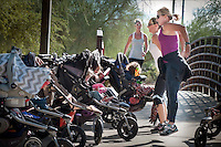 Instructor Jeana Barnett (purple), gets in a few extra repetitions on a drill while keeping the children happy as their moms skip-jump up a nearby path during their Fit4Mom class at Desert Horizon Park in Phoenix. The class uses portable equipment strollers and park landscape to help moms fit a workout into their busy schedules.