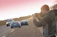 Teenage Boy Standing by Highway and Taking Photos of Risky Driving Past Cars