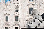 The facade of the Duomo (Cathedral) in Milan, Italy with a statue of a lion in front.