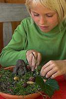Kinder basteln Zwergengärtchen, Zwergen-Gärtchen aus Naturmaterialien, Bastelei, Tonschale wird mit Moos ausgelegt, Ton, Eicheln, Kastanien, Äste und Blätter werden zum Dekorieren benutzt