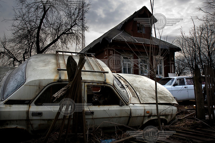 A disused car lays trashed in front of a wooden house on the road, near the town of Tver.