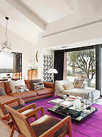 The purple 'Pamplona' rug by Carpet Diem injects bold colour into the the otherwise black and white colour scheme of the living area furnished with retro pieces