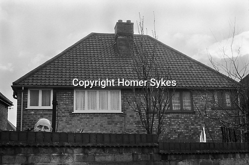Householder looks over wall at a demonstration, Manchester, England 1976