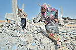 Najeeb Zaneen and Moyasar El Za'anen walk through the rubble of their home in Beit Hanoun, Gaza, which was destroyed by an Israeli air strike in 2014. They have received help in reestablishing their farm from International Orthodox Christian Charities, a member of the ACT Alliance.