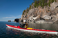 Sea kayaker on Lake Superior explores a rocky shoreline on Minnesota North Shore at Split Rock Lighthouse State Park.