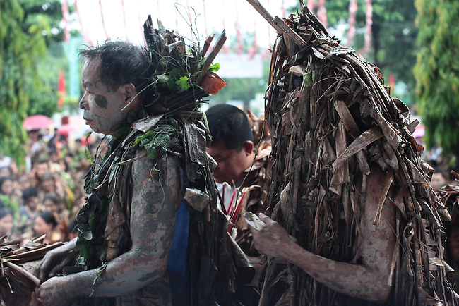 "People wait to deposit alms on the steps of the Catholic church during the annual Taong Putik, or ""mud people,"" festival in Bibiclat, on Luzon island, Philippines. The festival honors St. John the Baptist, and devotees smear themselves with mud and dress in cloaks made from banana leaves and vines, which symbolize the animal skins the saint wore in the Bible. June 24, 2011."