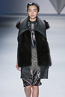 Xiao Wen Ju walks runway in a charcoal melton sleeveless coat with raccoon vest and structural collar over black vault print silk chiffon sleeveless dress with stand melton collar and crystal mesh apron, from the Vera Wang Fall 2012 Vis-a-gris collection, during Mercedes-Benz Fashion Week Fall 2012 in New York.