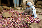 A girl sorts onions in a market in Lahore, Pakistan....