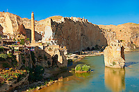 Remains of medieval Artukid Old Tigris Bridge – Built in 1116 by Artukid Fahrettin Karaaslan, the biggest in Anatolia at the time, with the old town Hasankeyf and its ruins on the cliffs abover the river Tigris. The minaret is of the El Rizk Mosque built 1409.  Turkey. 1