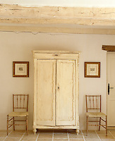 A painted white armoire is placed between a pair of simple chairs in this beamed hallway