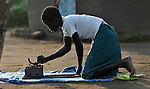 Twelve-year old Charty Moriba, a United Methodist in Pisak, a village in Southern Sudan, irons her school uniform in preparation for another day of learning. NOTE: In July 2011 Southern Sudan became the independent country of South Sudan.