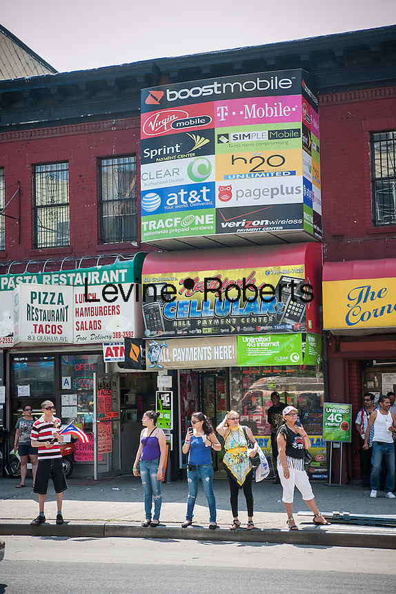 Cellular phone store in the busy Graham Avenue CBD in the Bushwick neighborhood of Brooklyn in New York on Sunday, June 2, 2013. As more and more hipsters move into the neighborhood the ethnicity of the area is changing.   (© Richard B. Levine)