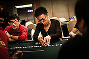 A poker player discreetly checks his cards on the poker table at the Galaxy Macau Hotel in Macau, China.