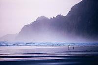 woman and dog on the beach at Manzanita Oregon with ocean spray and bluffs behind