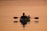 A kayaker watches the sunset in the fishing port of Menemsha in Chilmark, on the Massachusetts islands of Martha's Vineyard..........................