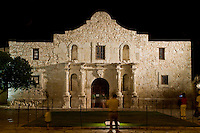 Tourists enjoying a nighttime view of the Alamo mission in San Antonio, Texas, historic landmark of the Texas Revolution.
