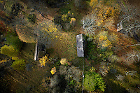 A view of a house in a forest with trees changing colour in Autumn in Kashubia.