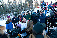 Fans and volunteers greet Martin Buser as he leads the 2011 Iditarod into McGrath on Tuesday.
