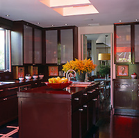 A narrow doorway connects the dining room with the kitchen in which the units and cabinets have been stained a dark red